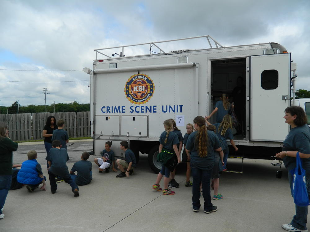 Kids looking at a crime scene unit